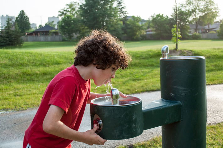 Hispanic boy with curly hair drinking from a water fountain in a park